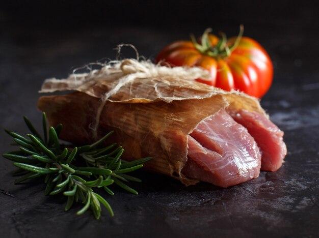 Кусочек сырого стейка из индейки с розмарином и помидорами на темном столе