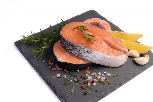Кусочек красной рыбы лосося на черной грифельной доске, изолированной на белом