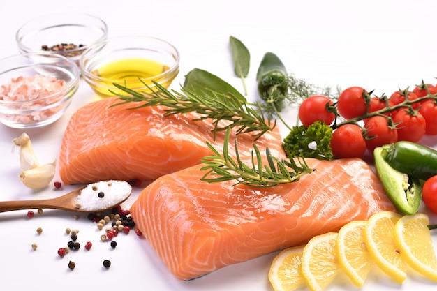 Ломтик красного лосося с кулинарными ингредиентами на белом