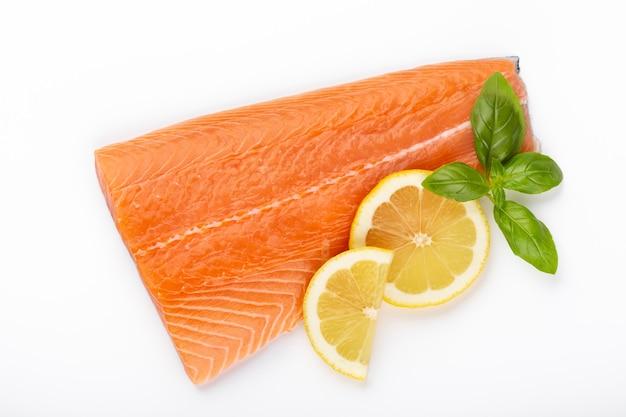 레몬, 바 질 흰색 배경에 고립 된 붉은 생선 연어의 조각. 평면도. 플랫 레이