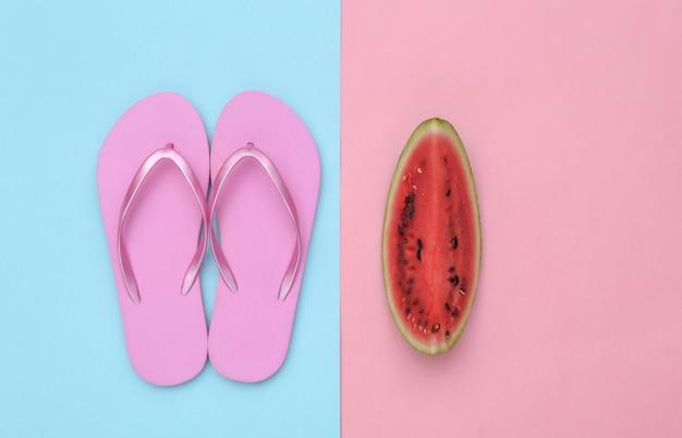 ピンクブルーの背景に熟したスイカとビーチサンダルのスライス。夏の楽しみ、ビーチでの休息。上面図。フラットレイ