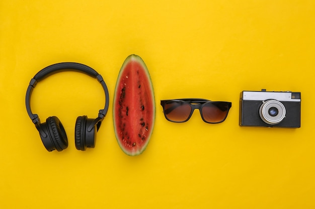 熟したスイカとサングラス、黄色の背景にカメラとステレオヘッドフォンのスライス。夏の楽しみ、旅行。上面図。フラットレイ