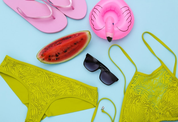 Кусочек спелого арбуза и купальник, пляжные аксессуары на синем фоне. летние развлечения, пляжный отдых. вид сверху. плоская планировка