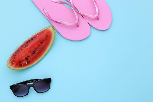 青の背景に熟したスイカ、サングラス、ビーチサンダルのスライス。夏の楽しみ、ビーチでの休息。上面図。フラットレイ。コピースペース