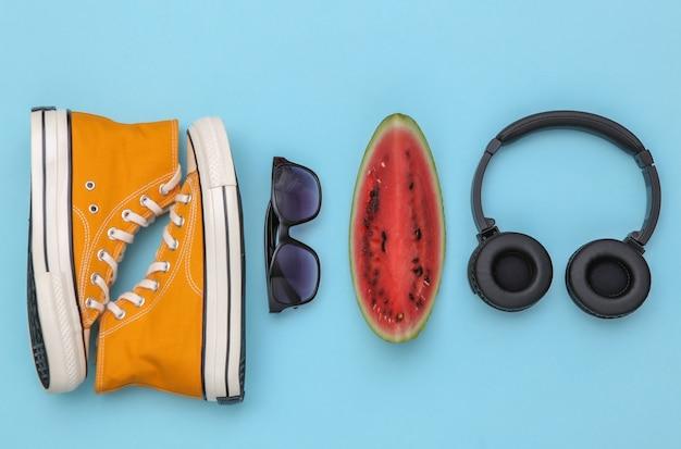 잘 익은 수박 조각, 선글라스, 운동화, 파란색 배경에 헤드폰. 여름 재미. 평면도. 플랫 레이
