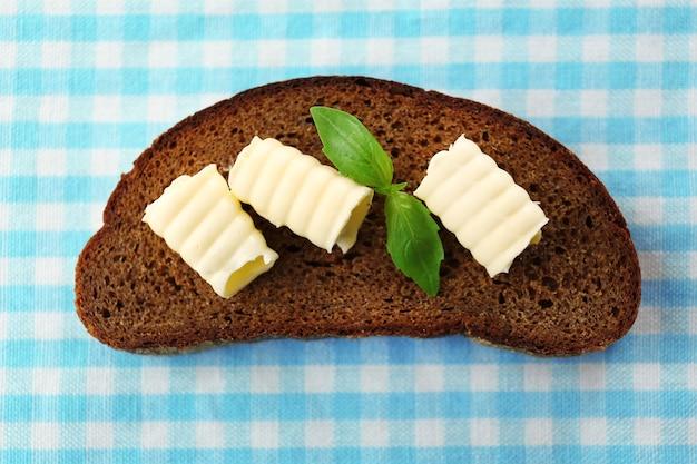 青と白のテーブルクロスにバターとライ麦パンのスライス
