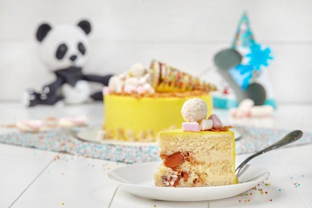 Кусочек бисквитного торта с заварным миндалем и вафельным шариком в кокосовой стружке