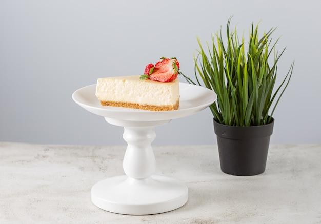 Кусочек клубничного чизкейка на белой тарелке на подставке для торта на белом фоне.