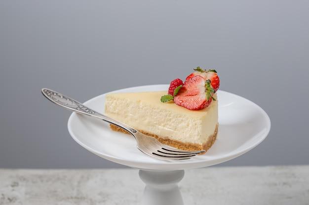Кусочек клубничного чизкейка на белой тарелке на подставке для торта