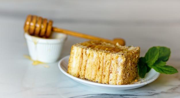 밝은 천연석 배경에 달콤한 수제 러시아 전통 겹겹이 쌓인 꿀 케이크 한 조각, 민트, 꿀, 나무 꿀 디퍼로 장식된 꼭대기 전망. 복사 공간