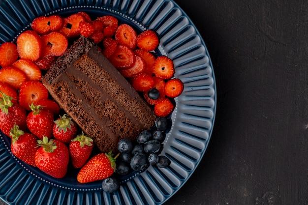 Кусочек вкусного шоколадного торта с нарезанной клубникой
