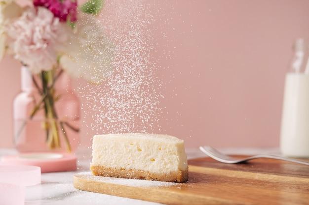 분홍색 배경에 꽃과 밀크가 있는 맛있는 홈메이드 치즈케이크 한 조각. 건강한 유기농 여름 디저트 파이 측면 보기