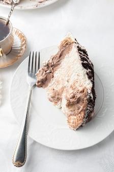 白い皿にティラマス ケーキのスライス。ホームメイド。フォークとコーヒー カップの近く。トップ ビュー ホワイト バック グラウンド。
