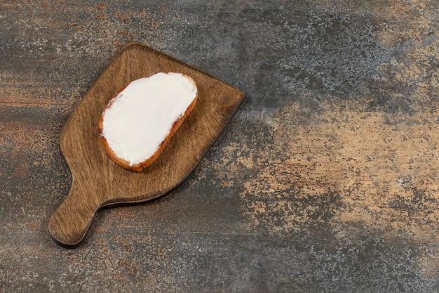木の板にサワークリームを添えたトーストのスライス。