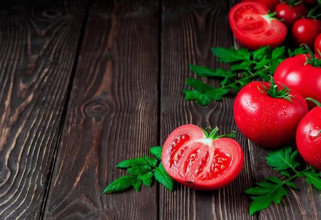 トマトと完熟した赤いトマトのスライスを暗い素朴な表面にクローズアップ