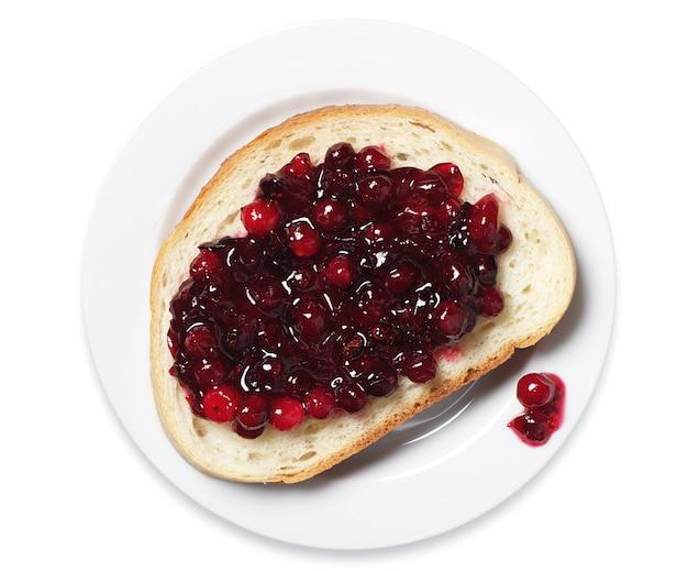 흰색 배경에 접시에 크랜베리 잼이 있는 흰 빵 조각