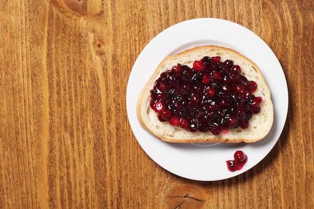 나무 배경에 접시에 크랜베리 잼과 흰 빵 조각. 평면도