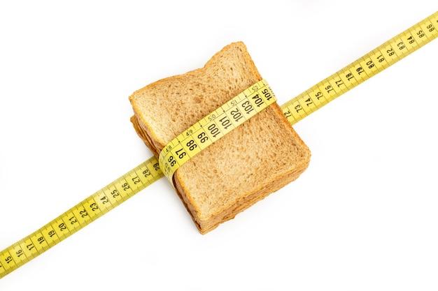 Кусочек хлеба из непросеянной муки с портновской мерной лентой
