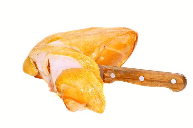 Нарежьте копченую курицу ножом. изолированные над белым.