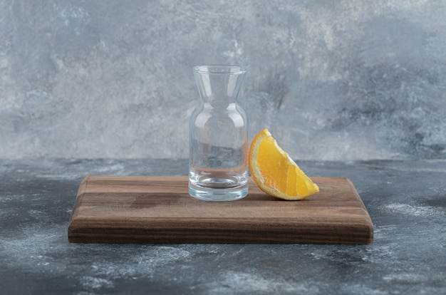Slice of orange and empty glass on wooden board.
