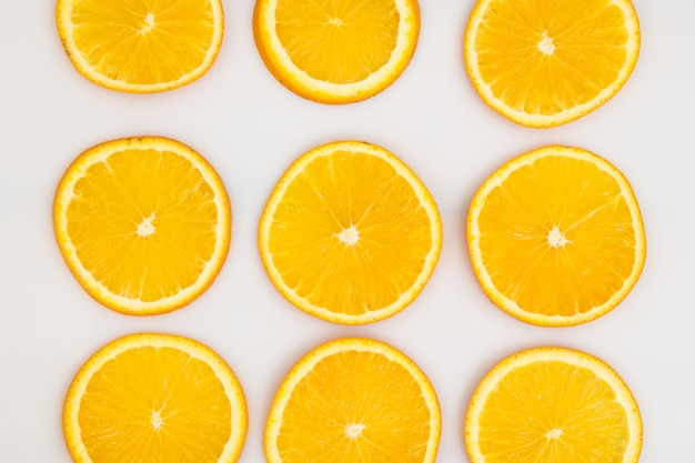 Slice orange fruit and place as pattern on white.