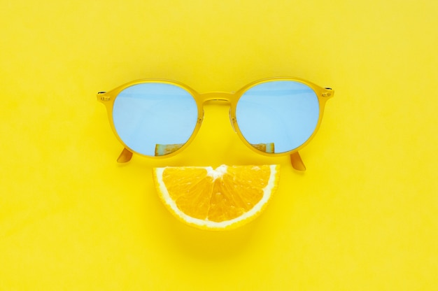Slice orange fruit sets as smile mouth and yellow sunglasses on yellow background.