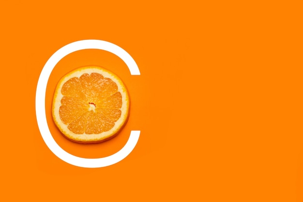 A slice of orange on an orange background with c letter drawed