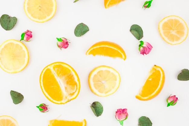 Slice of oranges; leaves and pink rose buds on white background