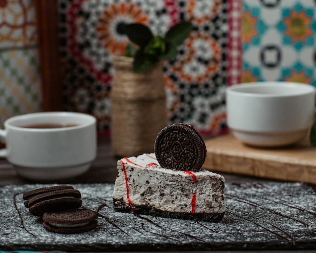 A slice of oreo cake with an oreo cookie on the top and a cup of tea
