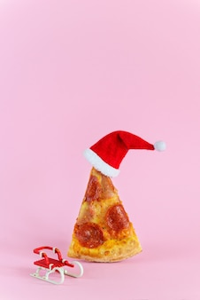 Slice of pepperoni pizza with santa hat and sleight beside