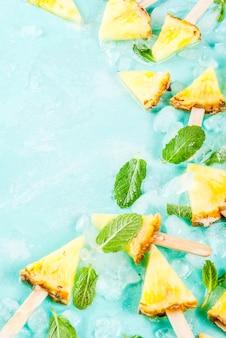 Ломтики ананасовых эскимо палочек и листьев мяты