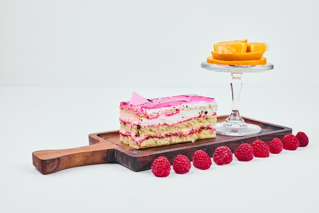 A slice of pink cake with fruits.