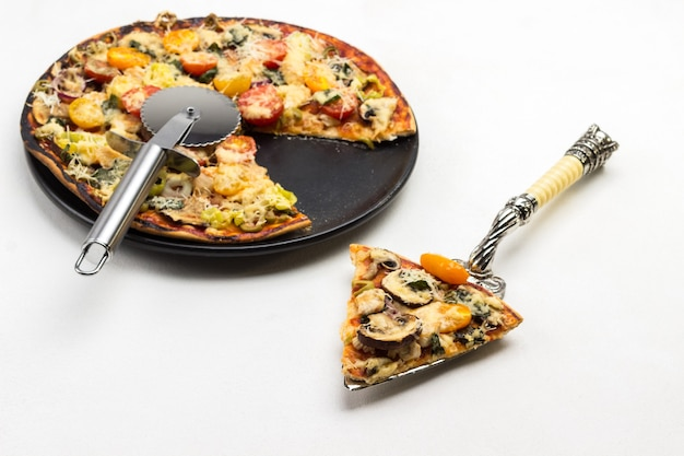 Slice of pizza on scoop and pizza on black plate
