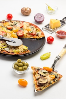 Slice of pizza on scoop. ready pizza on black plate. pizza cutter on pizza. grater with cheese. olives and tomatoes on table. white surface. top view
