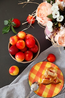 Slice of plum pie on plate. summer recipe. plums and flowers still life.