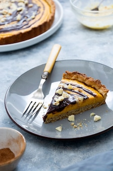 Slice of pumpkin pie. top view of squash tart. homemade autumn food. bakery background