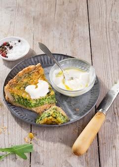 Slice quiche on a plate with arugula, onion, spinach, mozzarella, feta and sauce.