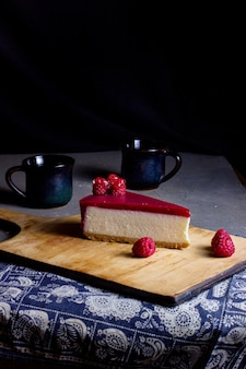 A slice of raspberry cheesecake placed on wooden cutting board
