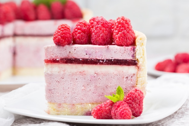 Slice of raspberry mousse cake with berry jelly and whipped cream