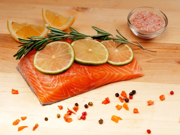 A slice of red fresh raw salmon fillet with lemon and rosemary and spices nearby. lie on a wooden cutting board. healthy food concept