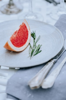 A slice of red grapefruit and green rosemary on a white plate with cutlery dusted with snow