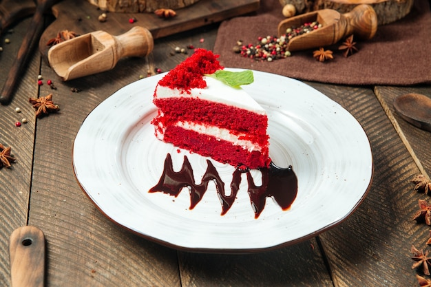 Slice of red velvet cake decorated with chocolate sauce on a white plate