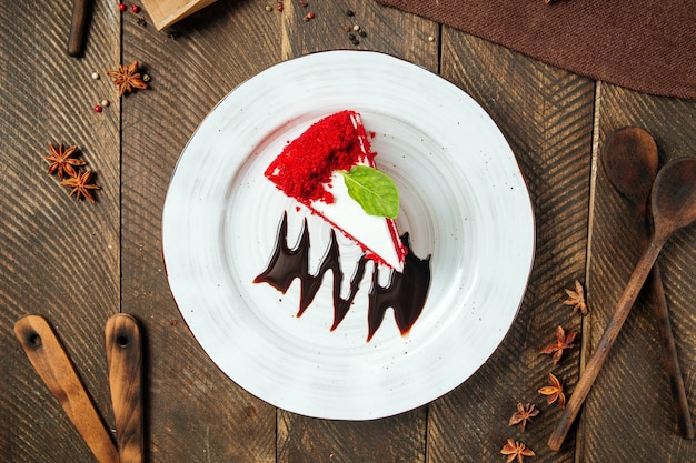 Slice of red velvet cake decorated with chocolate sauce