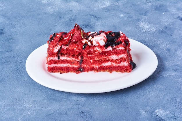 A slice of red velvet cake in a white plate