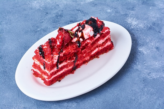 A slice of red velvet cake in a white plate.