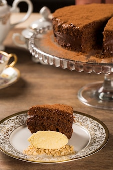A slice of rich chocolate cake with ice cream and coffee on the table