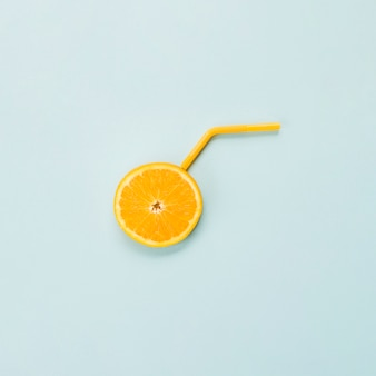Slice of ripe orange citrus and straw