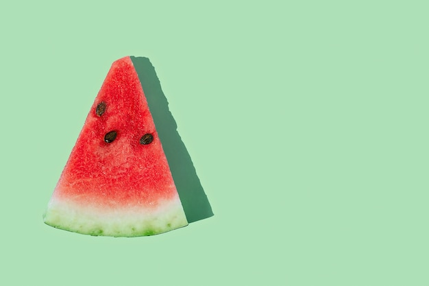 Slice of ripe watermelon on mint green background with copy space.