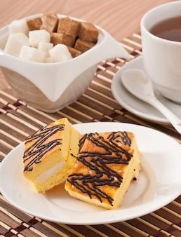 Slice of sponge cake with tea and sugar