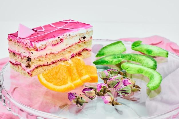 Una fetta di cheesecake alla fragola con frutta intorno.